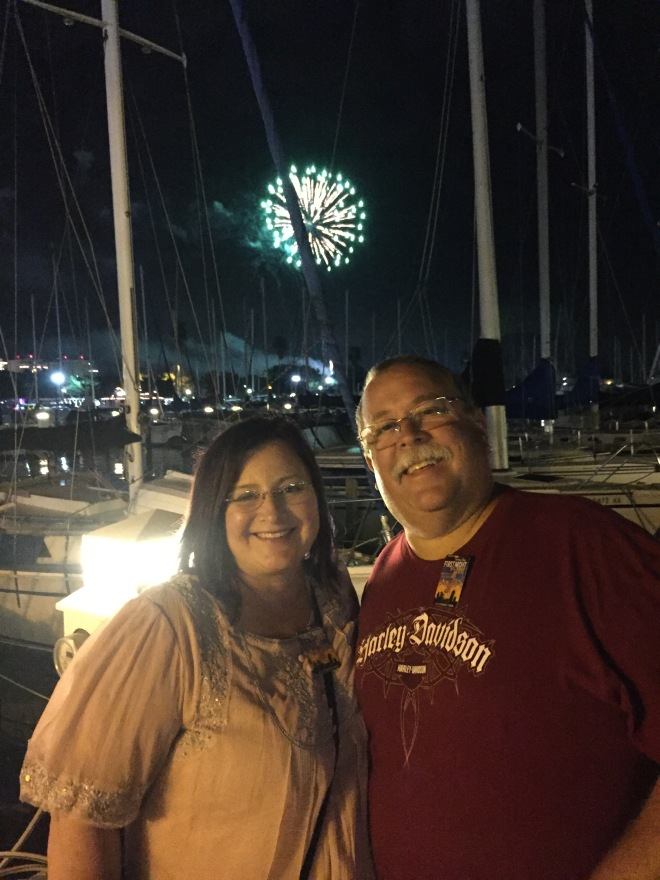 Steve and Peri smiling with fireworks and boat masts in the background